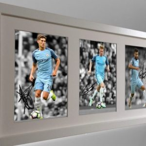 Sergio Aguero, Kevin De Bruyne, John Stones. Signed Manchester City Photograph Photo Picture. Black/White frame. Autographed.